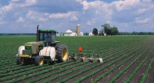 Agriculture - Chemical application on soybeans with a farmstead in the background / Illinois, USA.