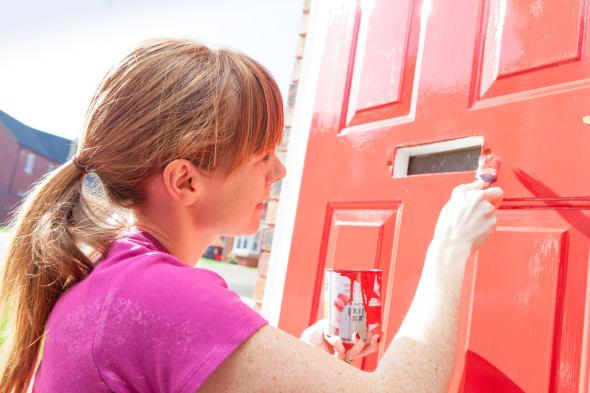 Woman in her thirties painting her front door red.