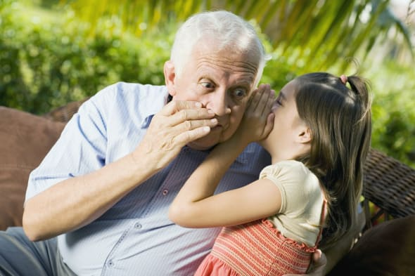 Close-up of a girl whispering into her grandfather's ear