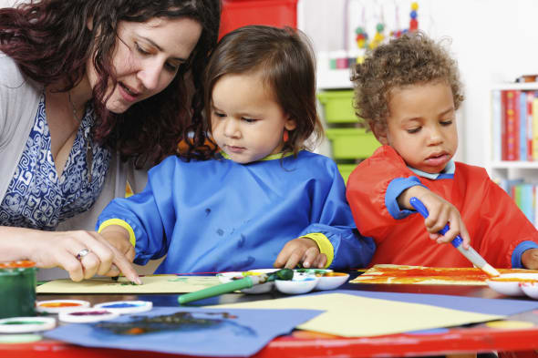 Close-up Of Carer Supervising Little Boys During Art And Craft