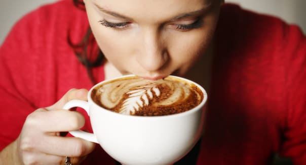 Pretty woman wearing red sipping a cafe mocha