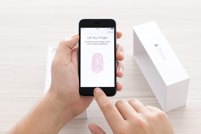 Man scans the fingerprint sensor Touch ID on iPhone 6