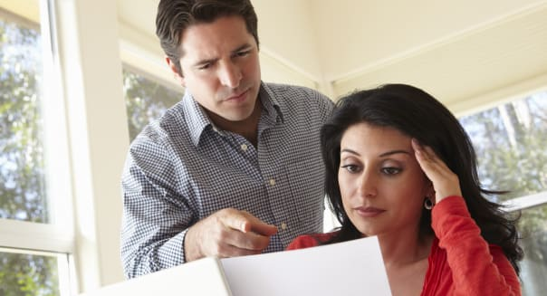 Hispanic Couple Working In Home Office Looking Worried