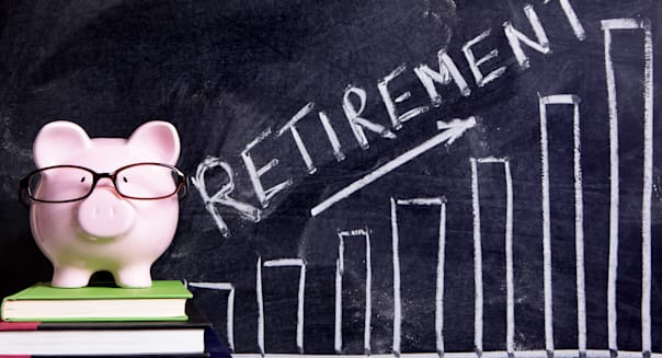 Pink piggy bank with glasses standing on books next to a blackboard with retirement savings message.  Sharp focus on the piggy b