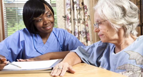 Senior woman visiting with nurse in her home