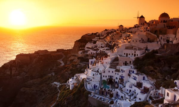 Sunset over whitewashed village on volcanic rim of caldera.