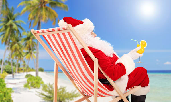 Santa Claus lying on a chair and drinking orange cocktail, enjoying on a sunny day, on a beach