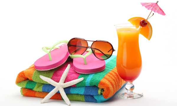 Beach accessories with swimming suit and tequila sunrise cocktail on white background.