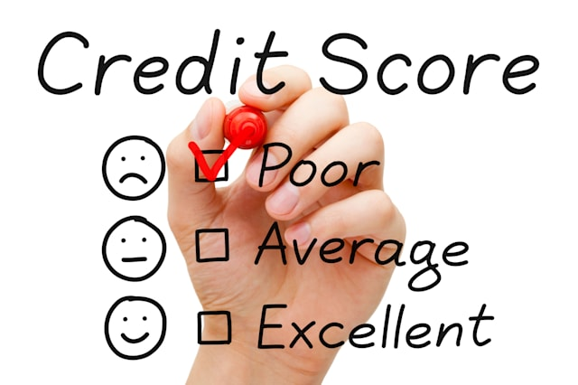 Hand putting check mark with red marker on poor credit score evaluation form.