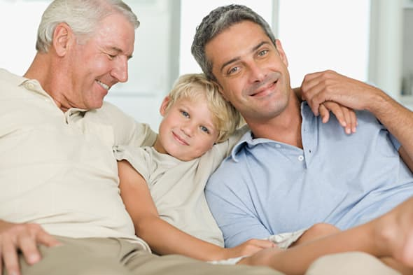 Little boy relaxing on couch with grandfather and father