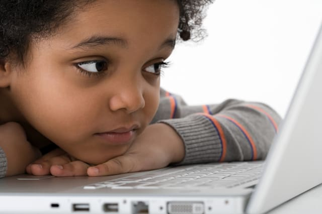 Boy leaning on laptop