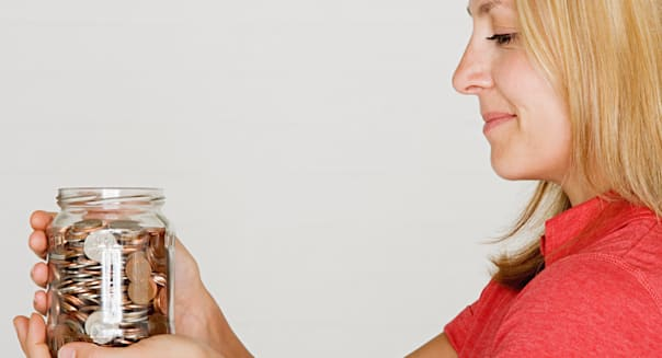 Woman holding jar of pennies