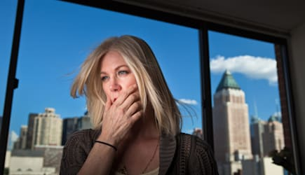 Mature woman looking anxious in office with cityscape visible behind