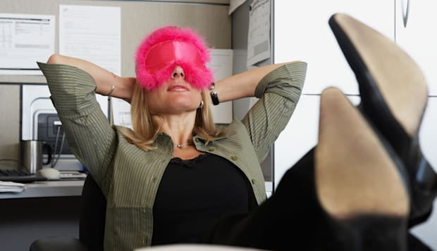 ARRHY3 Woman wearing eyemask in the office  Woman; wearing; eyemask; in; office; laziness; female; one; person; indoors; office;