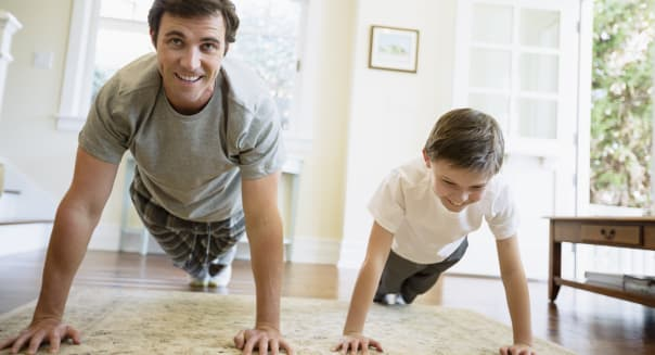 Father and sons doing push-ups in living room