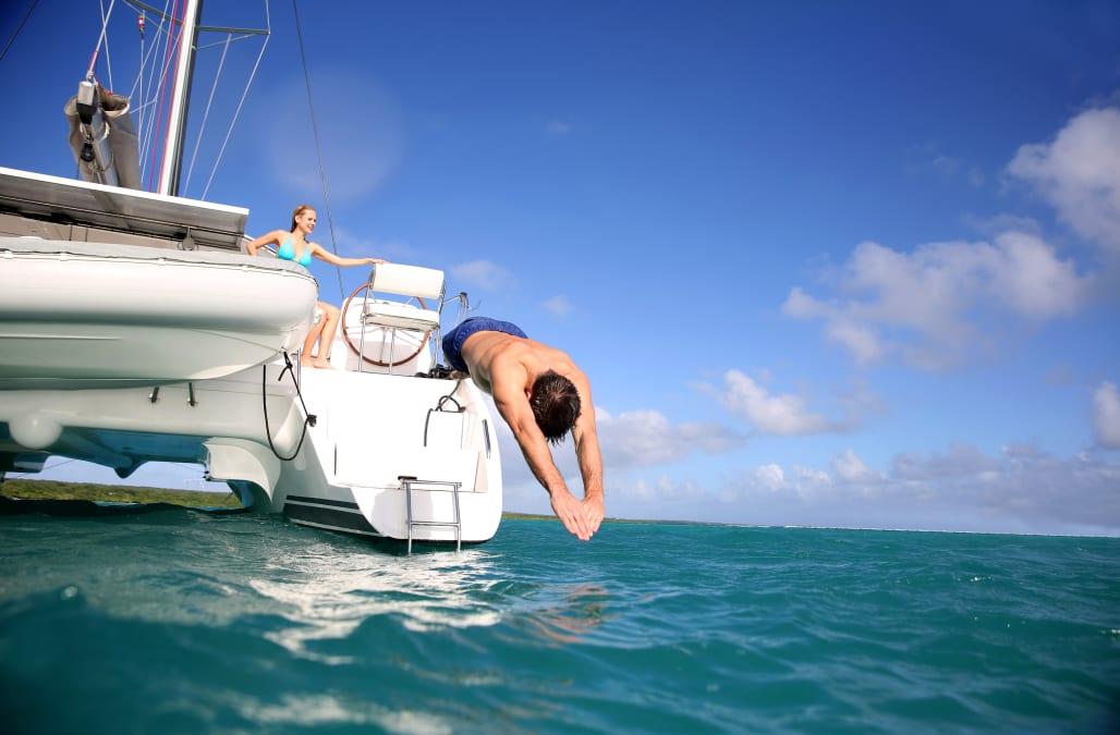 man diving from catamaran deck...