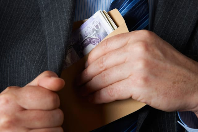 Businessman Putting Envelope Filled With Sterling In Jacket Pocket