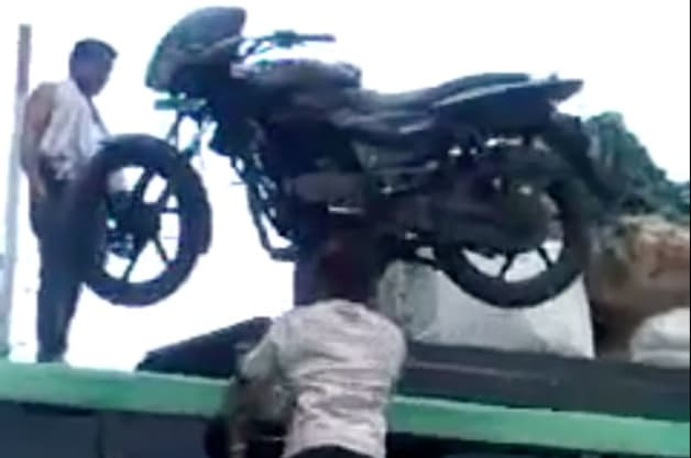 Watch this Indian man carry a motorcycle up a ladder on his head