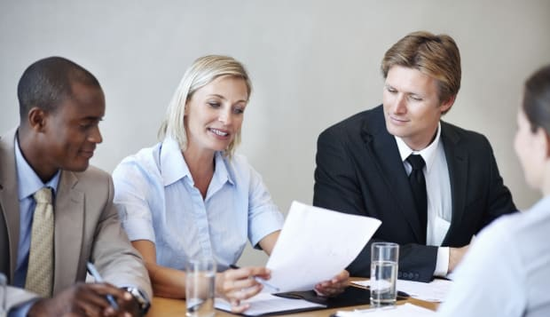 Panel of executives reading the resume of an applicant during her interview