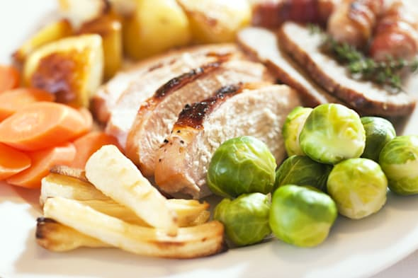 Christmas turkey dinner with Brussels sprouts, parsnips, carrots, roast potatoes, stuffing and pigs in blankets (sausages wrappe