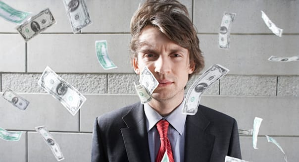 Busines man surrounded by falling money, outdoors, portrait