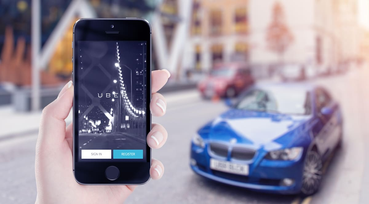 Varna, Bulgaria - May 25, 2015: Uber application startup page on Apple iPhone in female hand. Blurred street view on background.