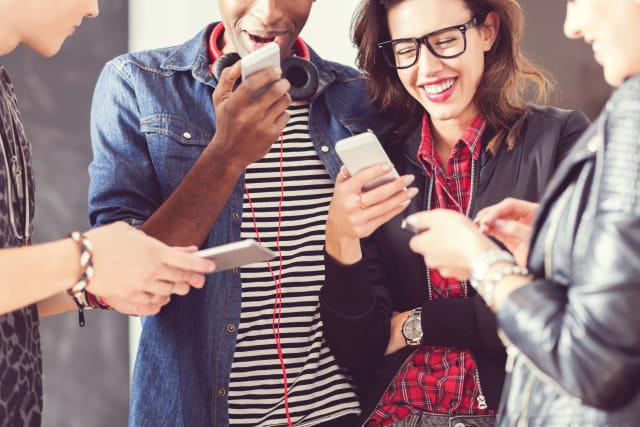 Friends using smart phones, close up of hands