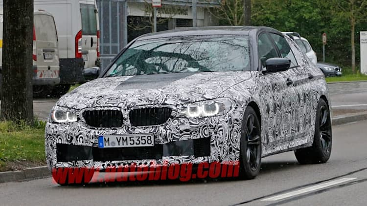 BMW M5 spied as camouflage striptease continues