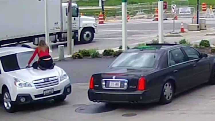 Woman thwarts car thieves by jumping on hood