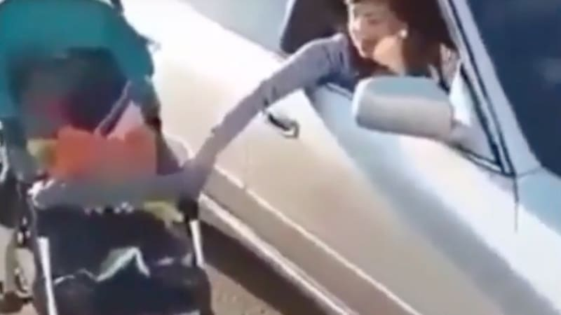 Woman caught pushing baby stroller while driving her car