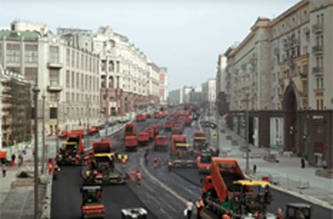 Swarm of trucks paves Russian road really quickly