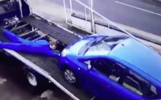 Mechanic tries to stop a car rolling off his flatbed but fails