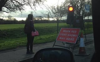 Obedient pedestrian waits with traffic by roadworks sign