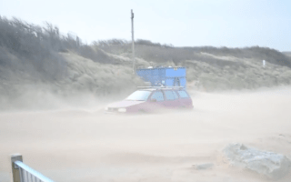 Car is buried in sand on Newquay beach as Storm Imogen hits
