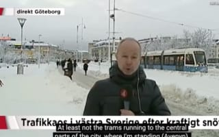 Reporter says snow halted trams as one goes past behind him