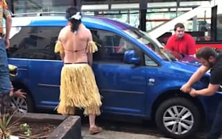 Grass-skirt wearing stag party lift car blocking the road