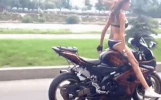 Half naked girl does yoga on a motorcycle