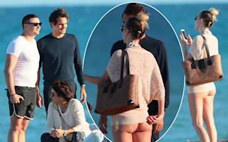 Roger Federer poses on Miami beach with fan whose bum is on show