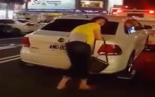 Woman clings desperately to car as it is towed away