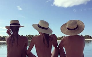 Miranda Kerr poses topless on the beach with friends