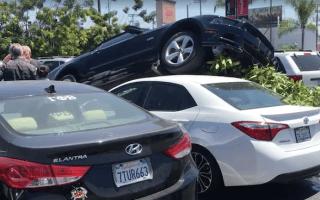 Ford Mustang mounts a Toyota Corolla in bizarre car park crash