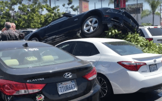 Ford Mustang mounts a Toyota Corolla in bizarre car park crash