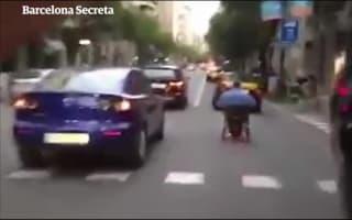 Wheelchair user speeds down busy street in Barcelona