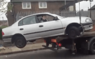Shocking moment man tries to drive his car off the back of a truck
