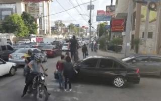 Pedestrians trample over car blocking crossing