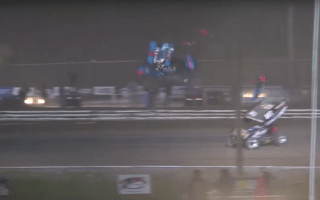 Racer crashes over fence and narrowly misses spectators