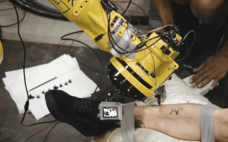 A car-making robot has been repurposed to give tattoos