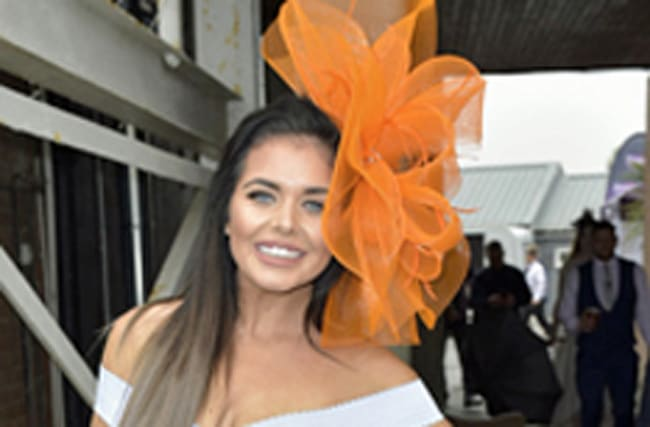 Scarlett Moffatt wears a huge orange fascinator to races