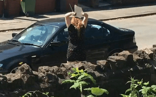 Scorned woman throws rock through 'cheating boyfriend's' car window