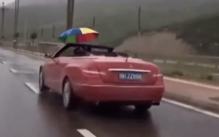 Man holds umbrella while driving convertible Mercedes in the rain